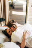woman with closed eyes kissing bearded boyfriend in bed