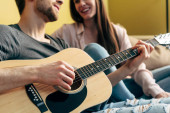 cropped view of bearded man playing acoustic guitar near happy girl in living room