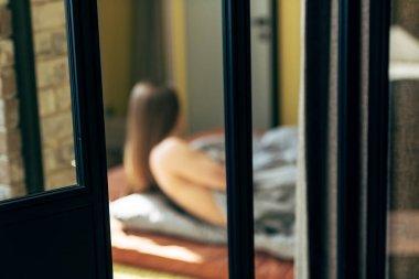 Selective focus of door near sensual woman lying in bedroom stock vector
