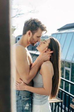 Selective focus of shirtless man hugging girlfriend on balcony stock vector