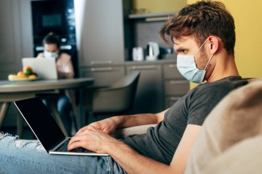 Selective focus of freelancer in medical mask using laptop with blank screen near girlfriend at home stock vector