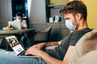 KYIV, UKRAINE - APRIL 22, 2020: selective focus of freelancer in medical mask using laptop with depositphotos website near girlfriend