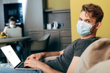 KYIV, UKRAINE - 22 Nisan 2020: Evdeki kız arkadaşının yanında google web sitesi olan dizüstü bilgisayarı kullanarak tıbbi maske takan serbest çalışanın seçici odağı
