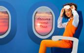 Fotografie usmívající se africká americká žena v oranžových retro šaty drží spací masku a sedí na sedadle na modrém pozadí s okénky a sny se vyplní ilustrace
