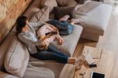 Photo Overhead view of mother clicking channels near kid lying on couch