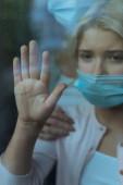 Szelektív fókusz a gyerek orvosi maszk megható gálák ablak közelében anya