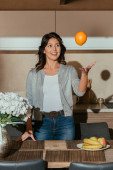 Selective focus of beautiful smiling woman throwing orange near flowers and fruits on kitchen table