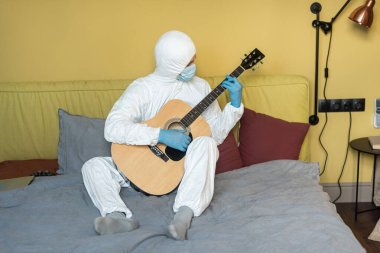 KYIV, UKRAINE - APRIL 24, 2020: Man in hazmat suit and medical mask playing acoustic guitar near laptop and joystick on bed stock vector