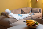 KYIV, UKRAINE - APRIL 24, 2020: Selective focus of man in hazmat suit and medical mask holding laptop near remote controller and gamepad on couch