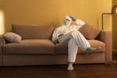 Man in medical mask, decontamination suit and latex gloves sitting on couch at home