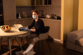 Photo Side view of man in medical mask and plaster bandage on led using laptop in kitchen