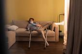Szelektív fókusz férfi orvosi maszk, latex kesztyű és gipsz kötés lábon tévénézés otthon