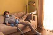 Fogyatékos férfi orvosi maszkban és gipszkötésben a lábán filmet néz mankók közelében otthon