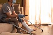 Vágott kilátás férfi orvosi maszk és törött láb kattintó csatornák otthon