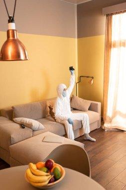 KYIV, UKRAINE - 24 Nisan 2020: Tehlikeli madde giysisi ve tıbbi maske giymiş bir adamın evdeki kanepede joystick tutmasının seçici odak noktası