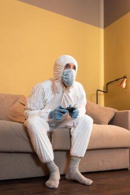 KYIV, UKRAINE - 24 Nisan 2020: Tehlikeli madde giysisi giyen ve sağlık maskeli bir adamın oturma odasında video oyunu oynaması