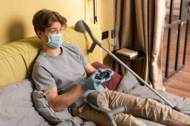 KYIV, UKRAINE - 24 Nisan 2020: Tıbbi maskeli engelli adam ve yatak odasındaki koltuk değneklerinin yanında oyun tahtası tutan lateks eldivenler