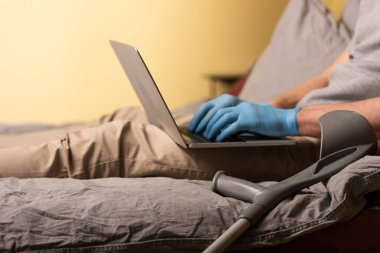 Cropped view of crutch near disabled man in latex gloves using laptop on bed stock vector