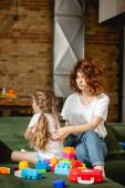 Lockige Mutter blickt beleidigte Tochter in der Nähe von Bauklötzen an