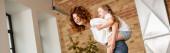 panoramatický záběr kudrnaté matky piggybacking roztomilý dcera