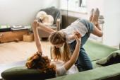 kudrnatá matka leží na pohovce, zvedá roztomilé dítě a drží se za ruce v obývacím pokoji
