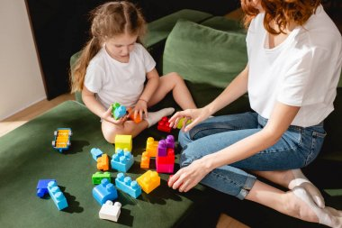 Curly mother and cute daughter playing building blocks in living room stock vector