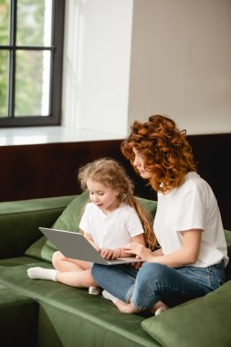 Redhead mother holding laptop near cute daughter in living room stock vector