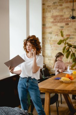 selective focus of redhead mother talking on smartphone while holding folder near daughter at home