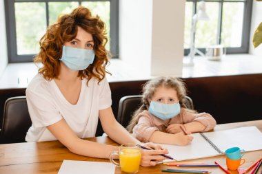 Mother in medical mask near daughter drawing at home stock vector