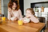 veselá matka a dcera drží lžíce v blízkosti misky s kukuřičnými vločkami a sklenicemi pomerančového džusu