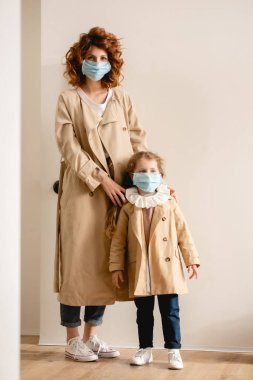 Curly mother and cute daughter in medical masks standing in trench coats stock vector