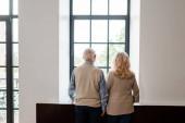 zpět pohled na rozrušený starší pár dívající se oknem domů na karanténu