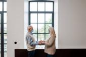 starší pár v lékařských maskách držící se za ruce a stojící u okna během vlastní izolace