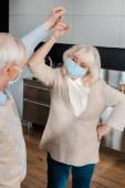 glückliches älteres Paar in medizinischen Masken tanzt zu Hause während der Selbstisolierung