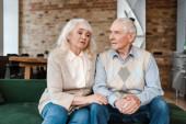 rozrušený starší pár sedí doma na vlastní izolaci