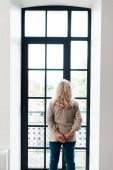 Zadní pohled na starší ženu stojící u okna doma během vlastní izolace