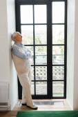 starší muž se zkříženýma rukama stojící u okna během karantény