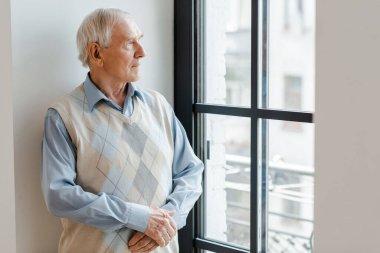 Sad lonely man looking through window during quarantine stock vector