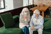Kranke ältere Frau und Mann in medizinischen Masken sitzen während der Coronavirus-Epidemie auf dem Sofa