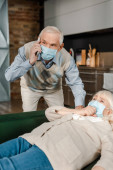 Photo worried elderly man in medical mask calling doctor with smartphone while ill wife lying on sofa during self isolation