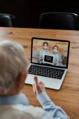 oříznutý pohled na staršího muže ukazujícího palec nahoru a mající videochat s vnoučaty v lékařských maskách s nápisem zůstat doma během vlastní izolace