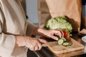 oříznutý pohled na starší ženu krájející zeleninu na palubě