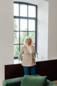 Glückliche ältere Frau steht während der Selbstisolierung am Fenster