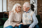 Fotografie sad senior couple hugging on sofa during self isolation