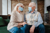 Photo sad elderly couple in medical masks sitting at home during self isolation