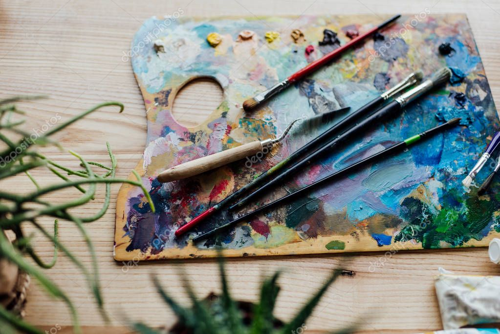 Palette of artist with paint brushes