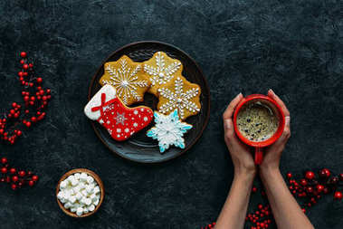 hands with christmas gingerbreads and coffee