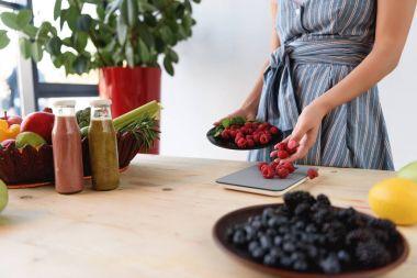 woman weighting raspberries