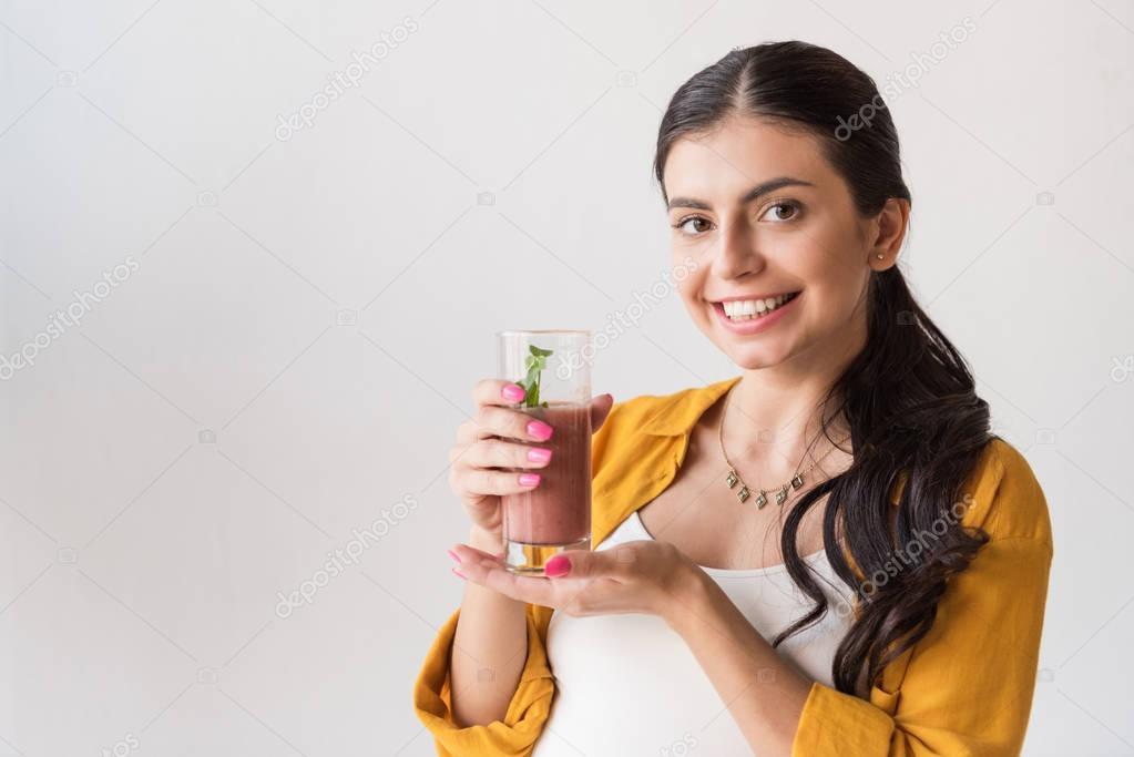 smiling woman showing detox drink