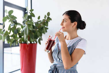 thoughtful woman with detox drink
